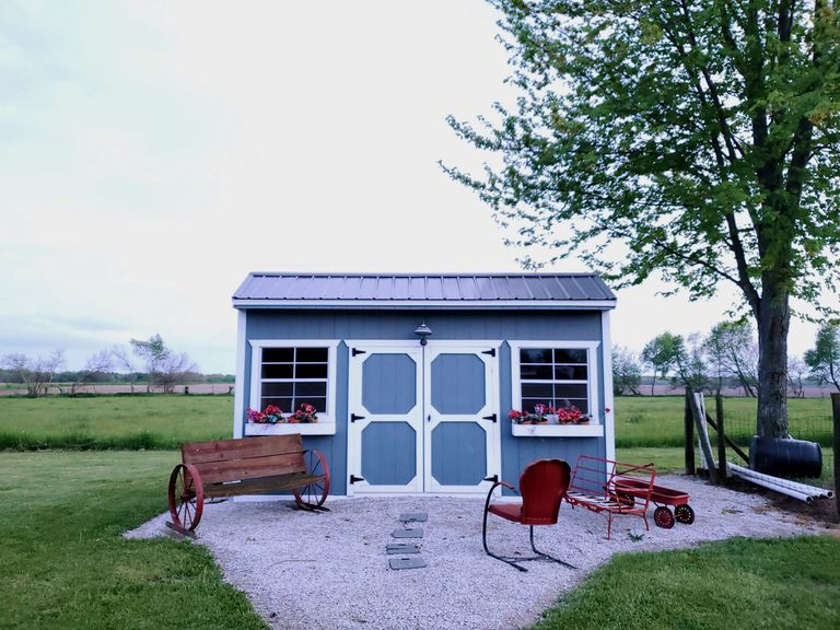 Blue and white tiny house with red lawn furniture outside