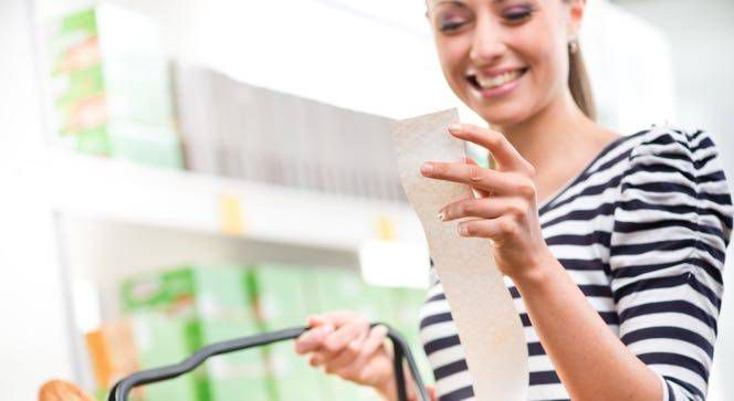 woman looking at her grocery receipt