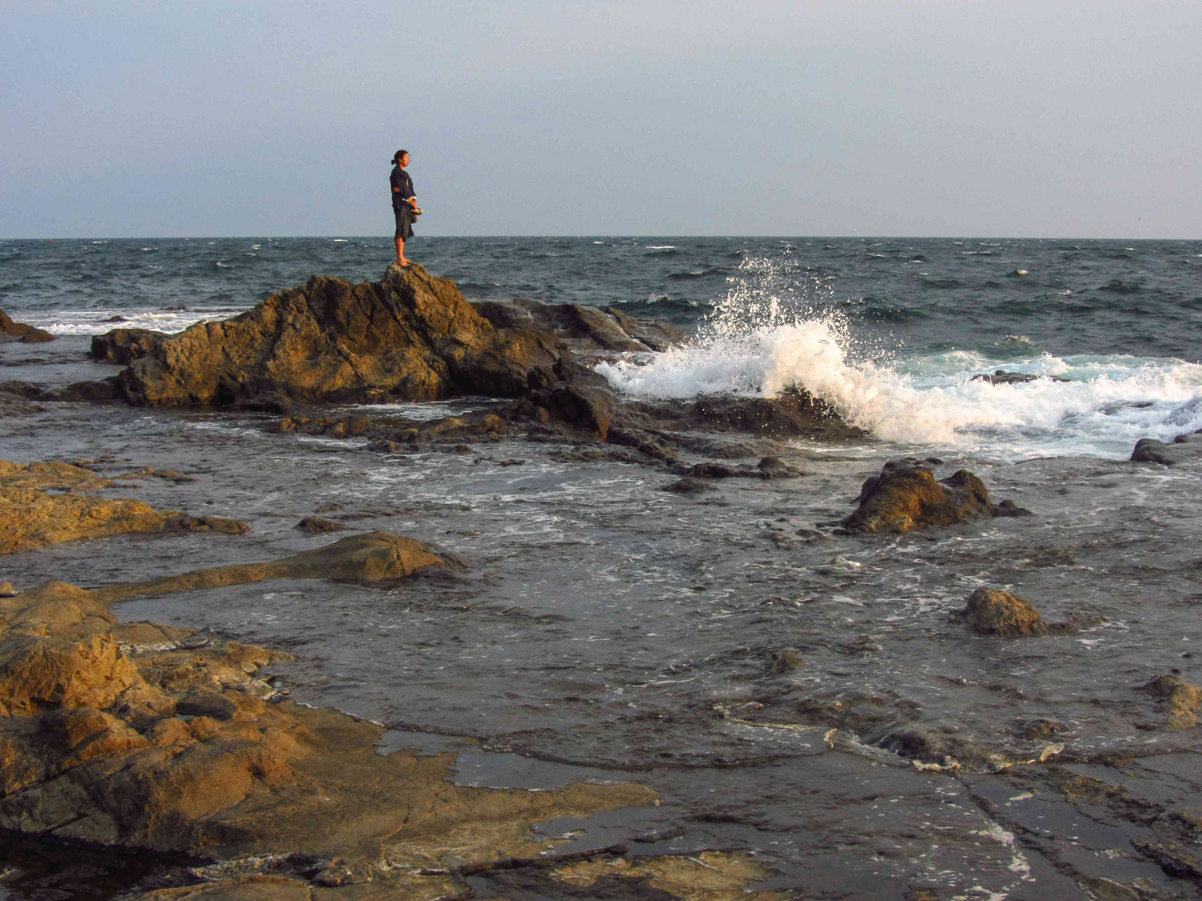 person stands alone on craggy rock while waves crash around them