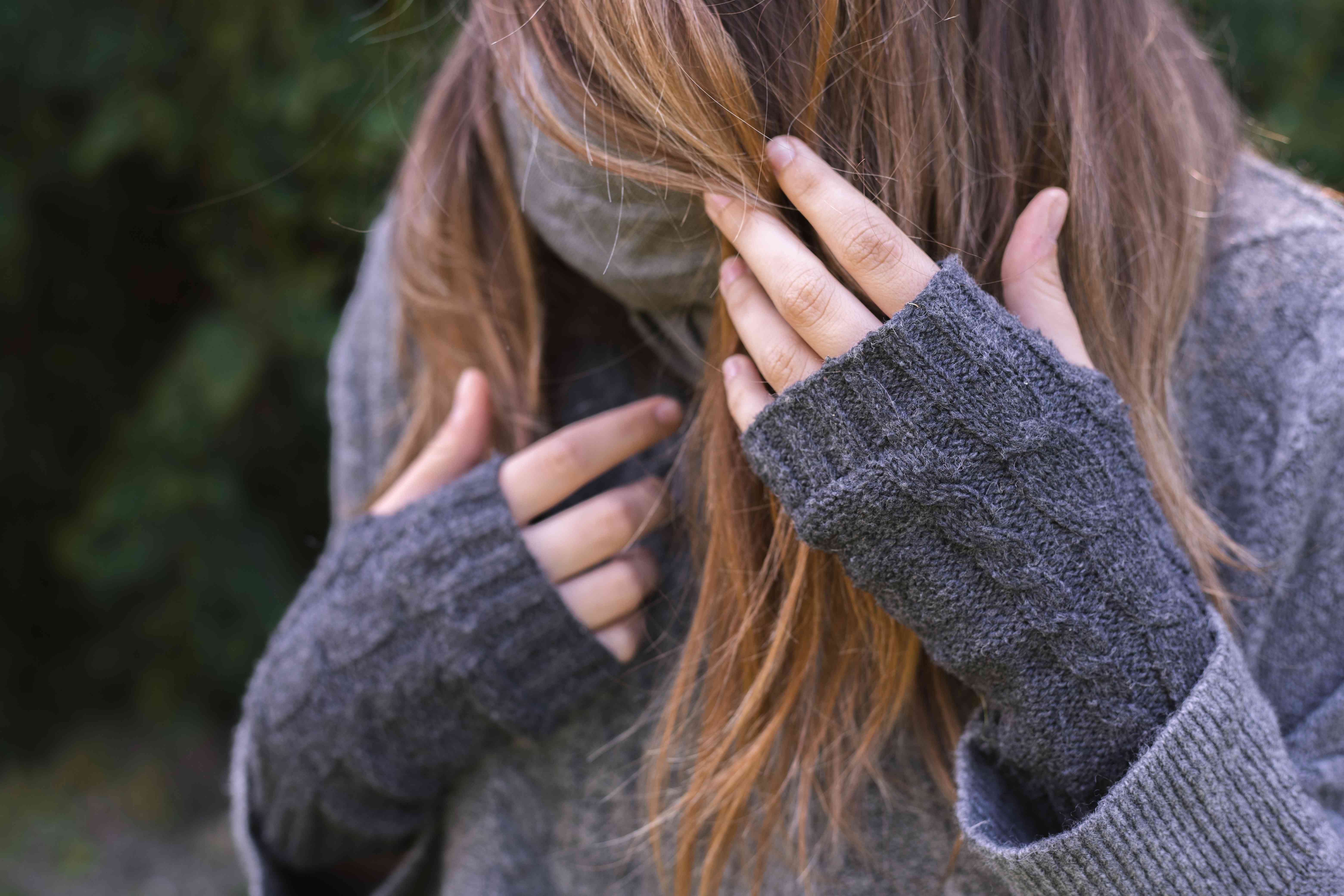 old gray sweater turned into fingerless gloves worn on model with long hair