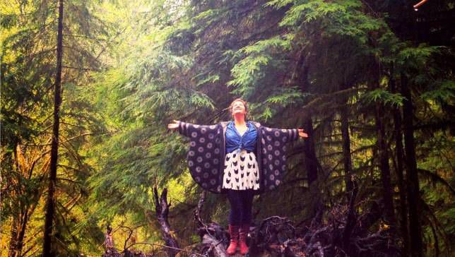 Person poses with outstretched arms in Olympic temperate rain forest