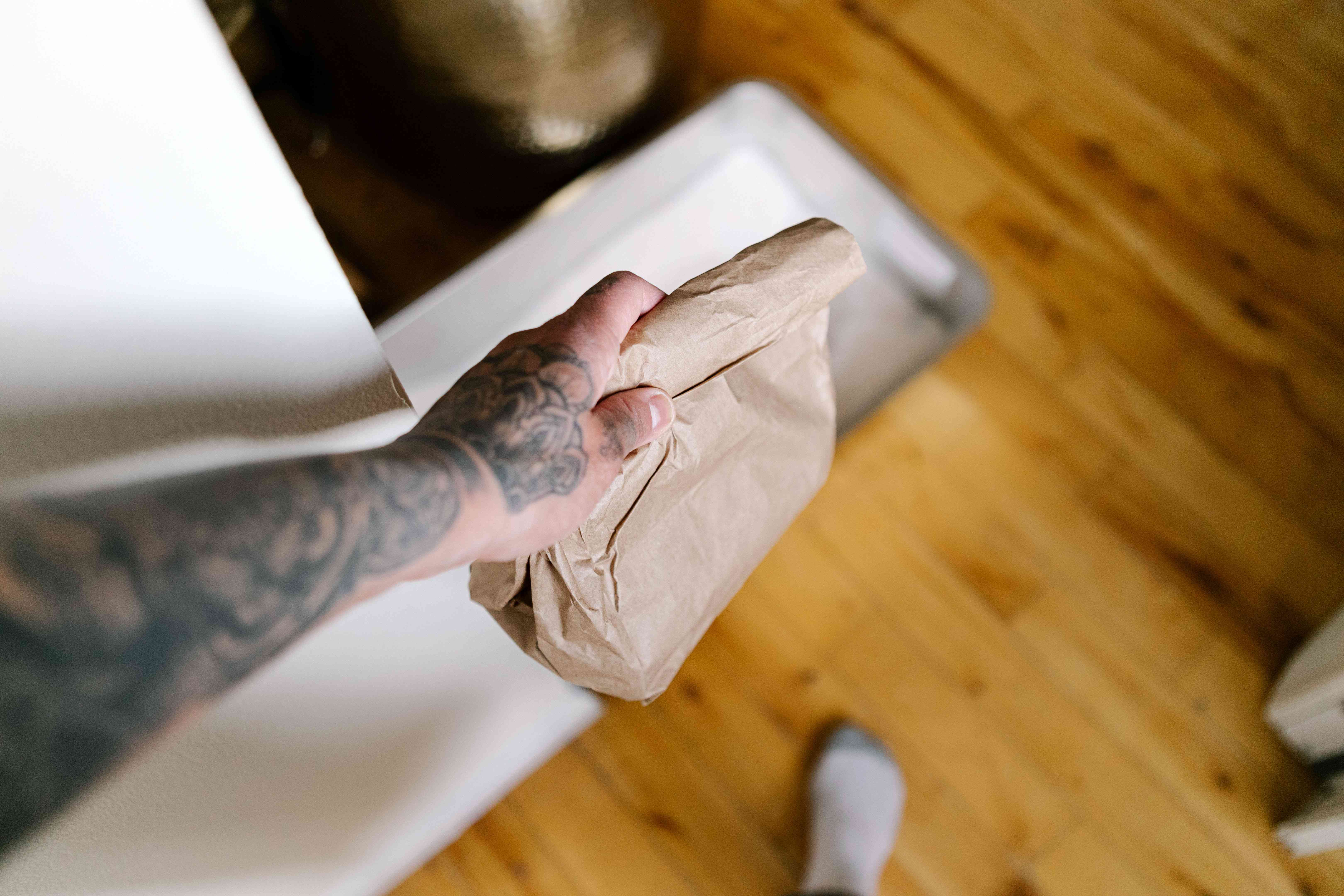 tattooed hand carries brown paper bag with cat waste past litter box
