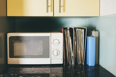 Two large folders full of recipe sheets and two recipe books on the kitchen counter.
