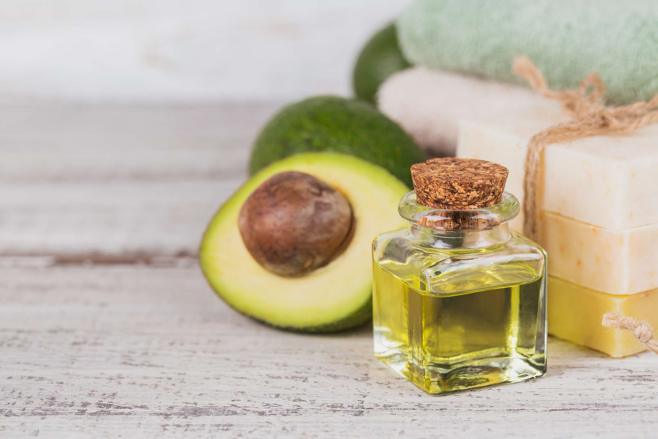 Avocado oil in a small bottle surrounded by a slice avocado and soaps.