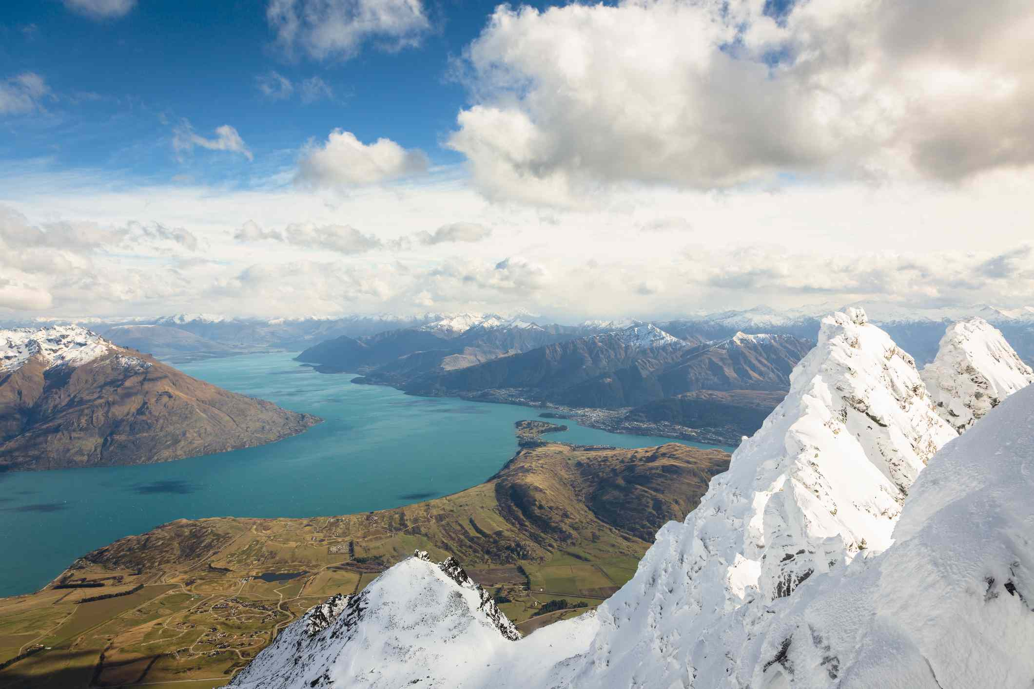Blue skies and fluffy what clouds above the turquoise water of Lake Wakatipu, surrounded by green and brown hills, with the snow-covered mountains of The Remarkables mountain range in the foreground