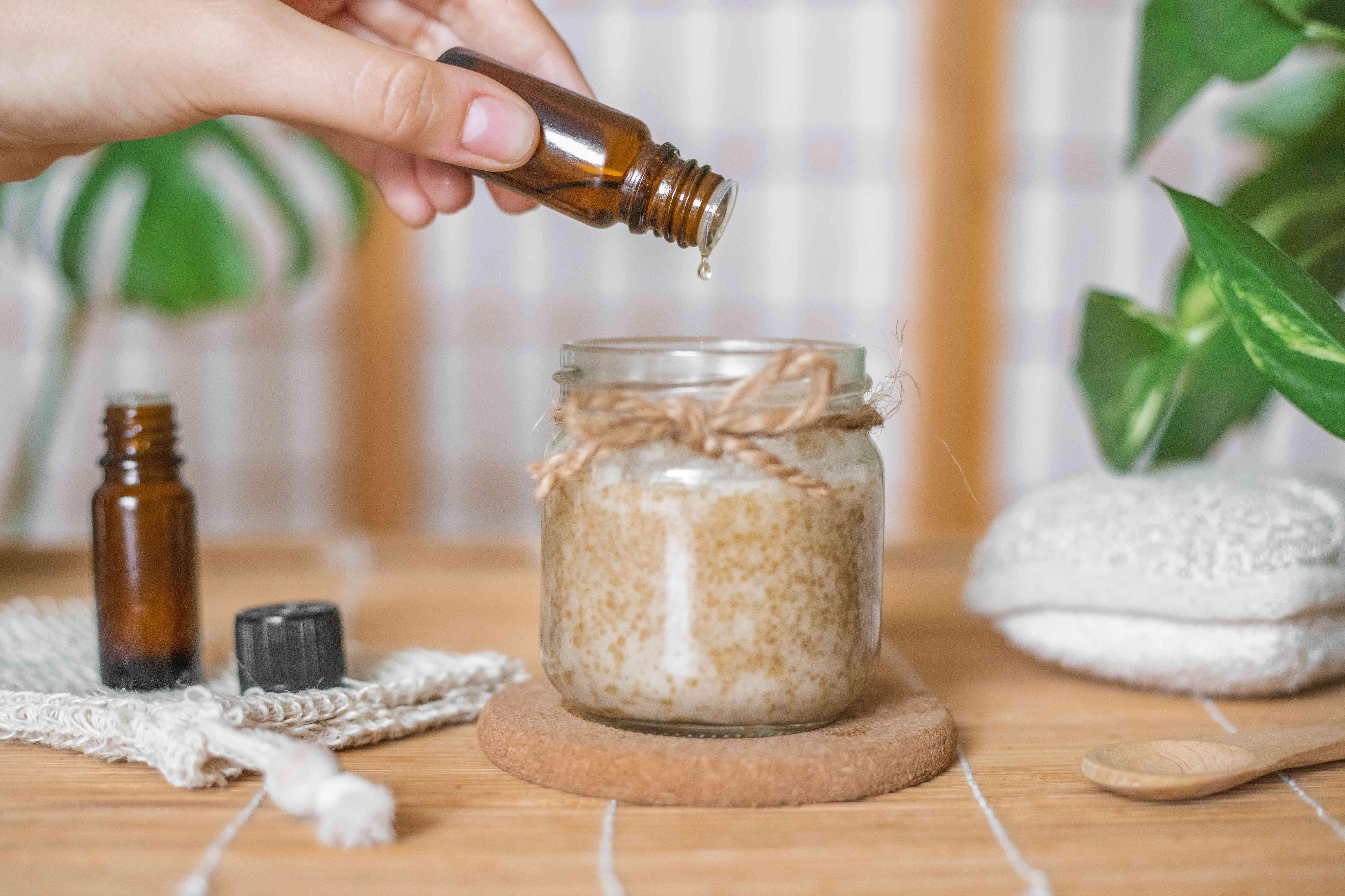 hand adds drop of essential oil to diy homemade coconut sugar scrub in glass jar
