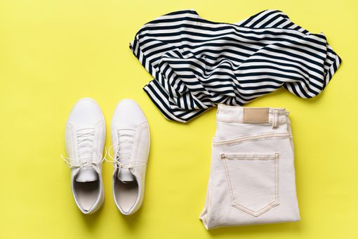 Female white sneakers and jeans, striped t-shirt on yellow background with copy space. Top view. Summer fashion, capsule wardrobe concept. Creative flat lay
