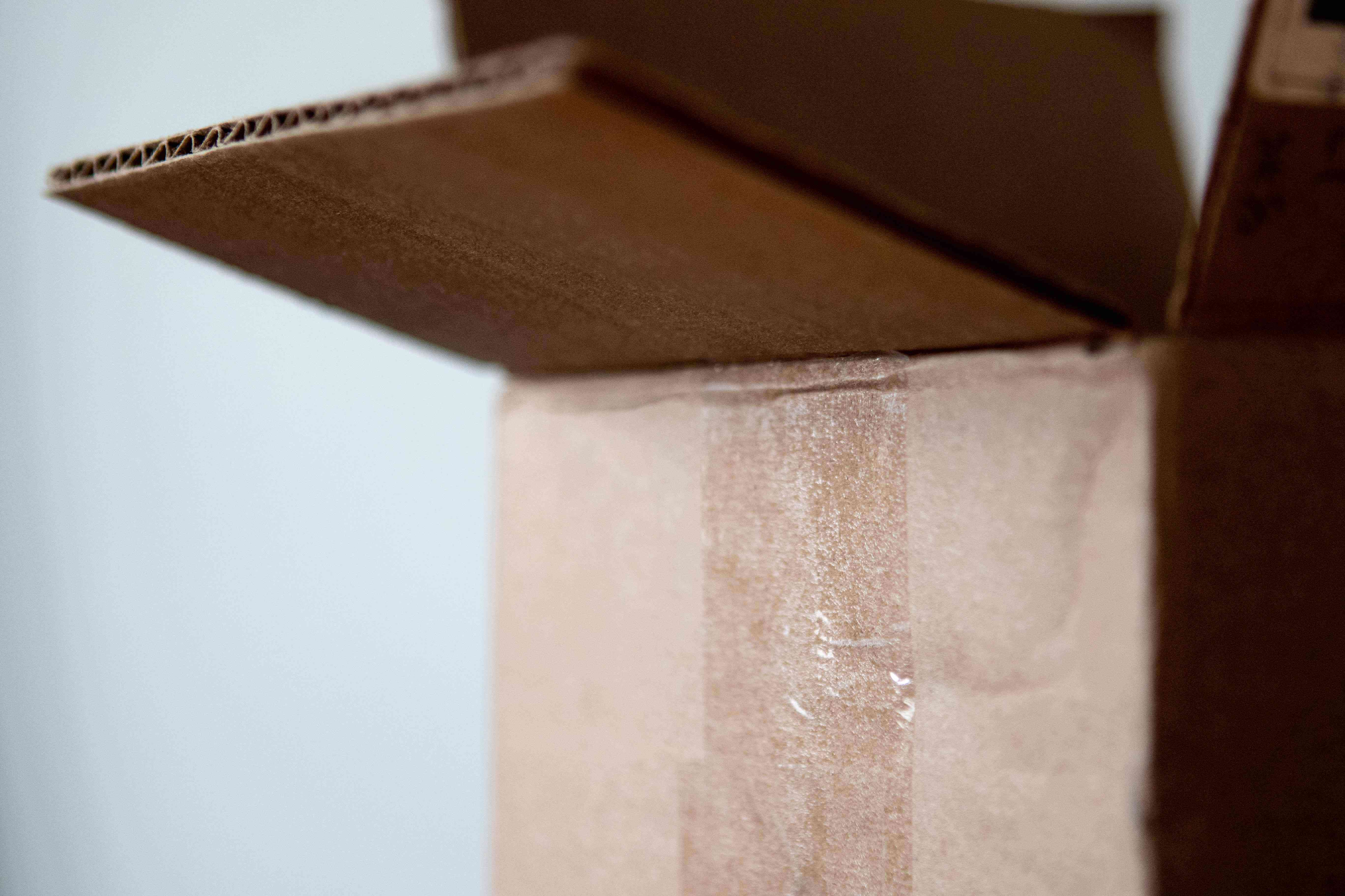 partial view of open cardboard box with clear tape attached