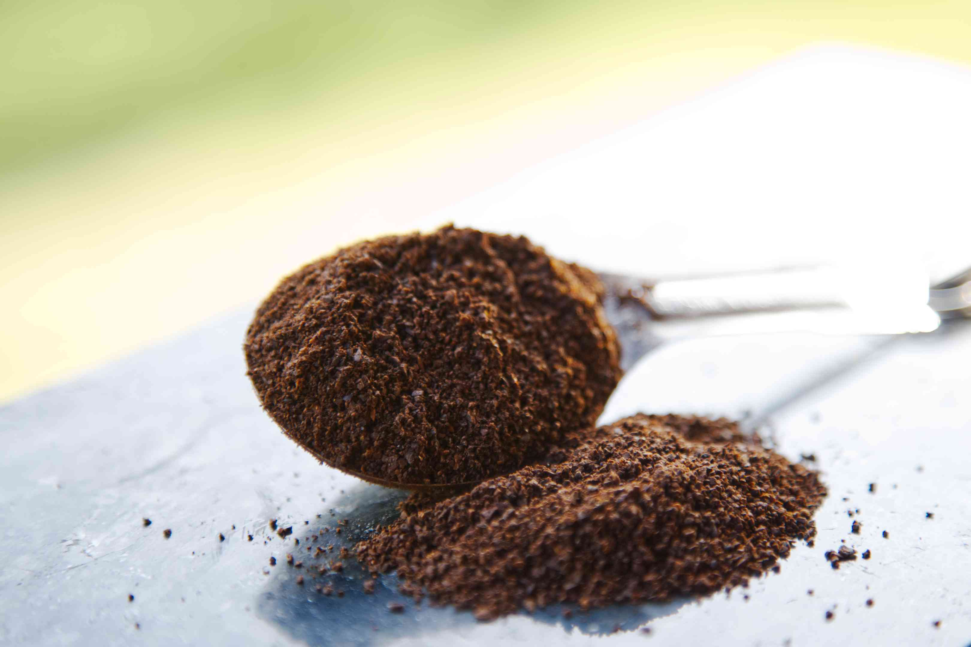 metal spoon filled with coffee grounds spilling onto table