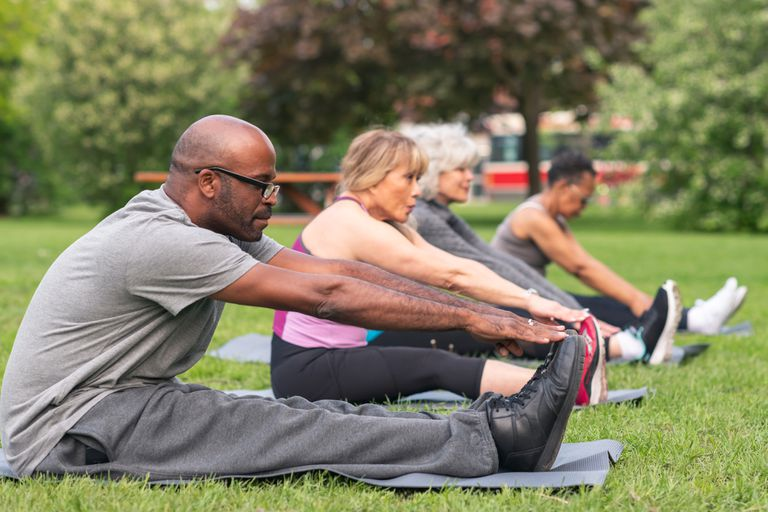 Four seniors stretching in a park