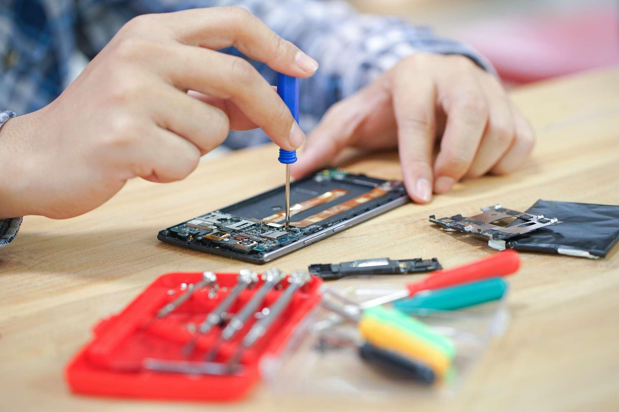 Hands repairing an electronic.