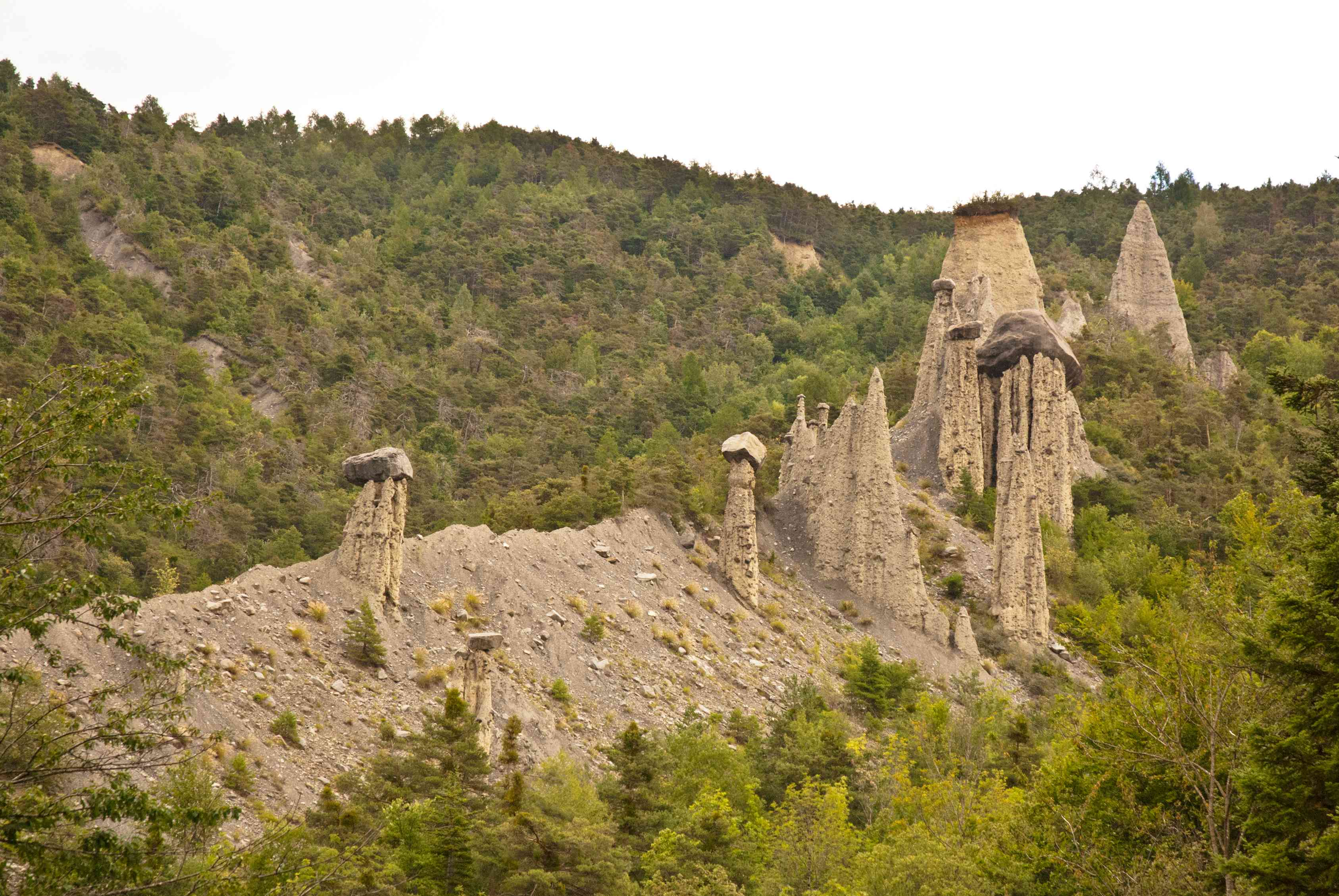 Row of hoodoos surrounded by green trees in Pontis, France.