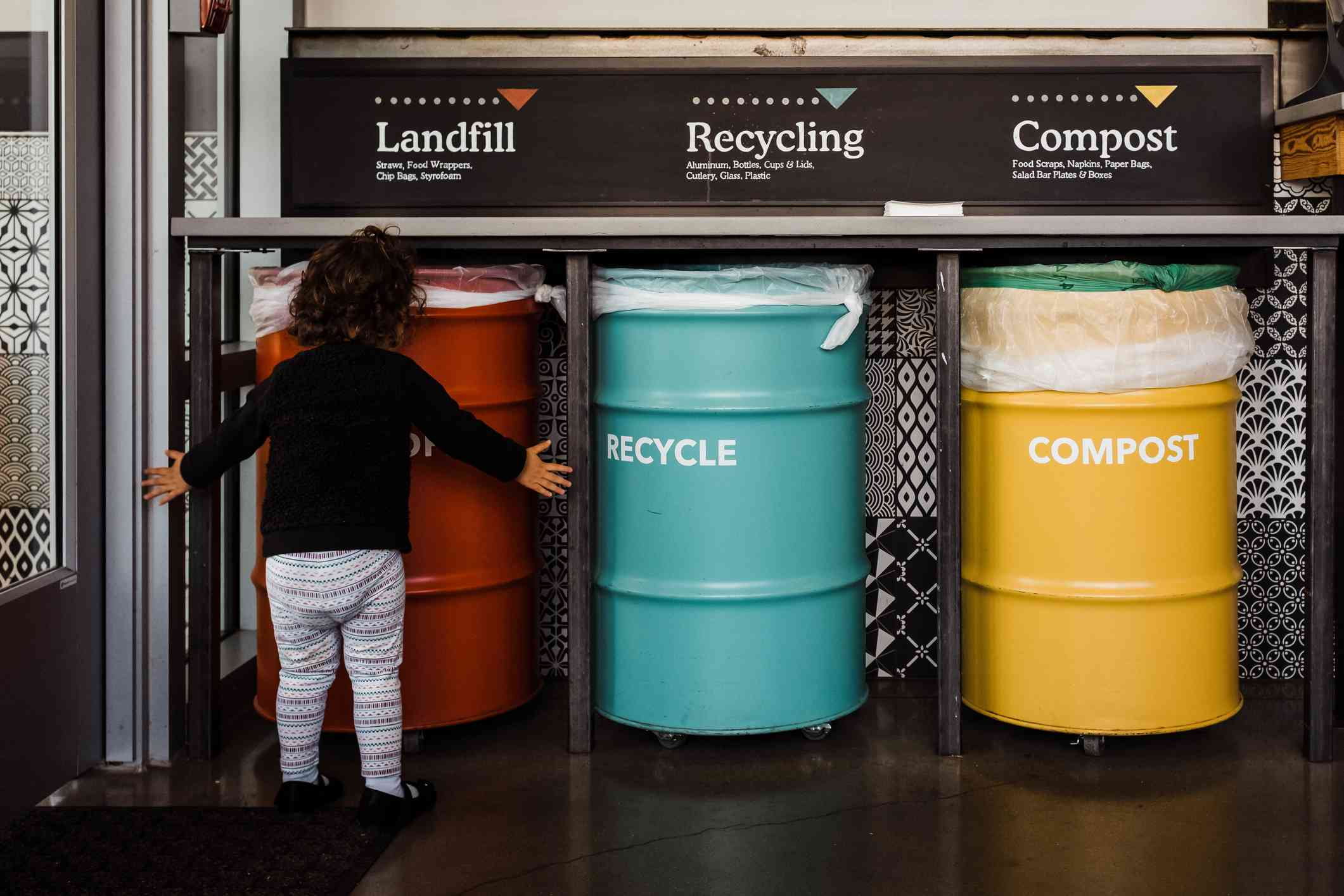 Small child standing in front of three large bins labeled: landfill (red), recycling (blue), and compost (yellow).