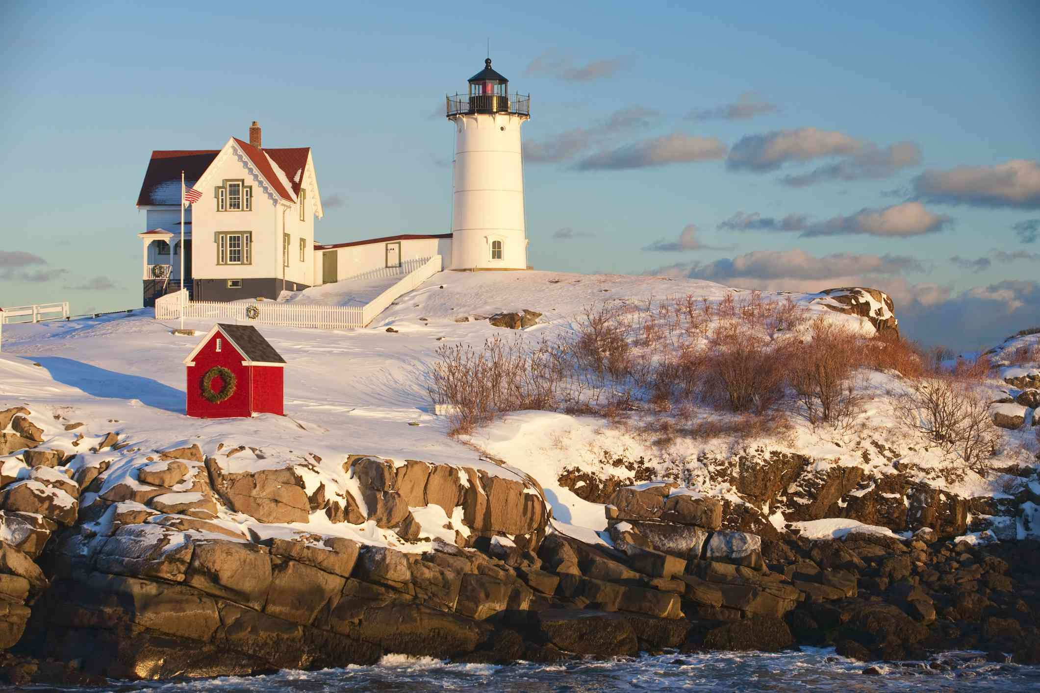 Cape Neddick Lighthouse with snow covering the base of the lighthouse and surrounding rocks