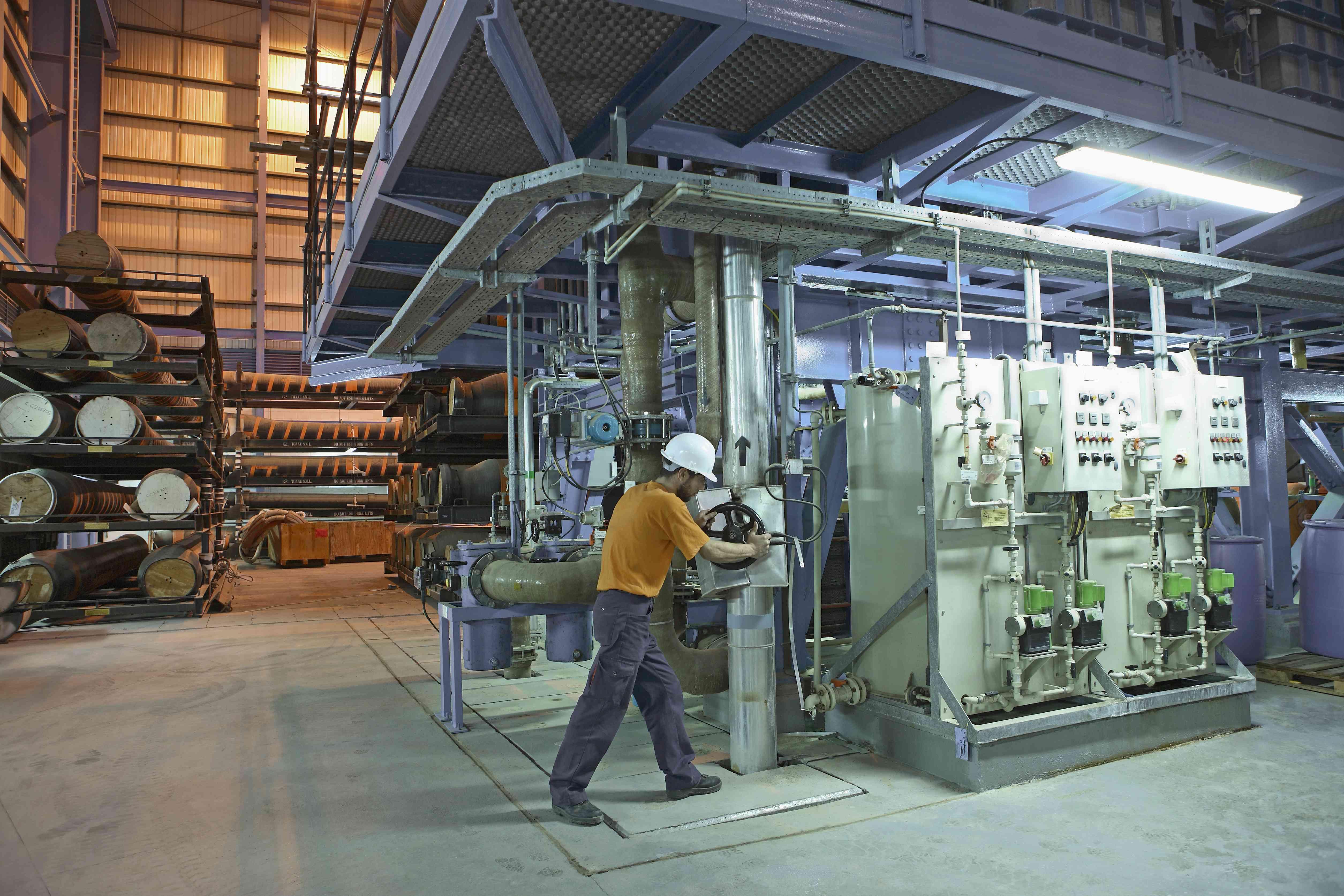 Technician closing valve desalination plant in power station