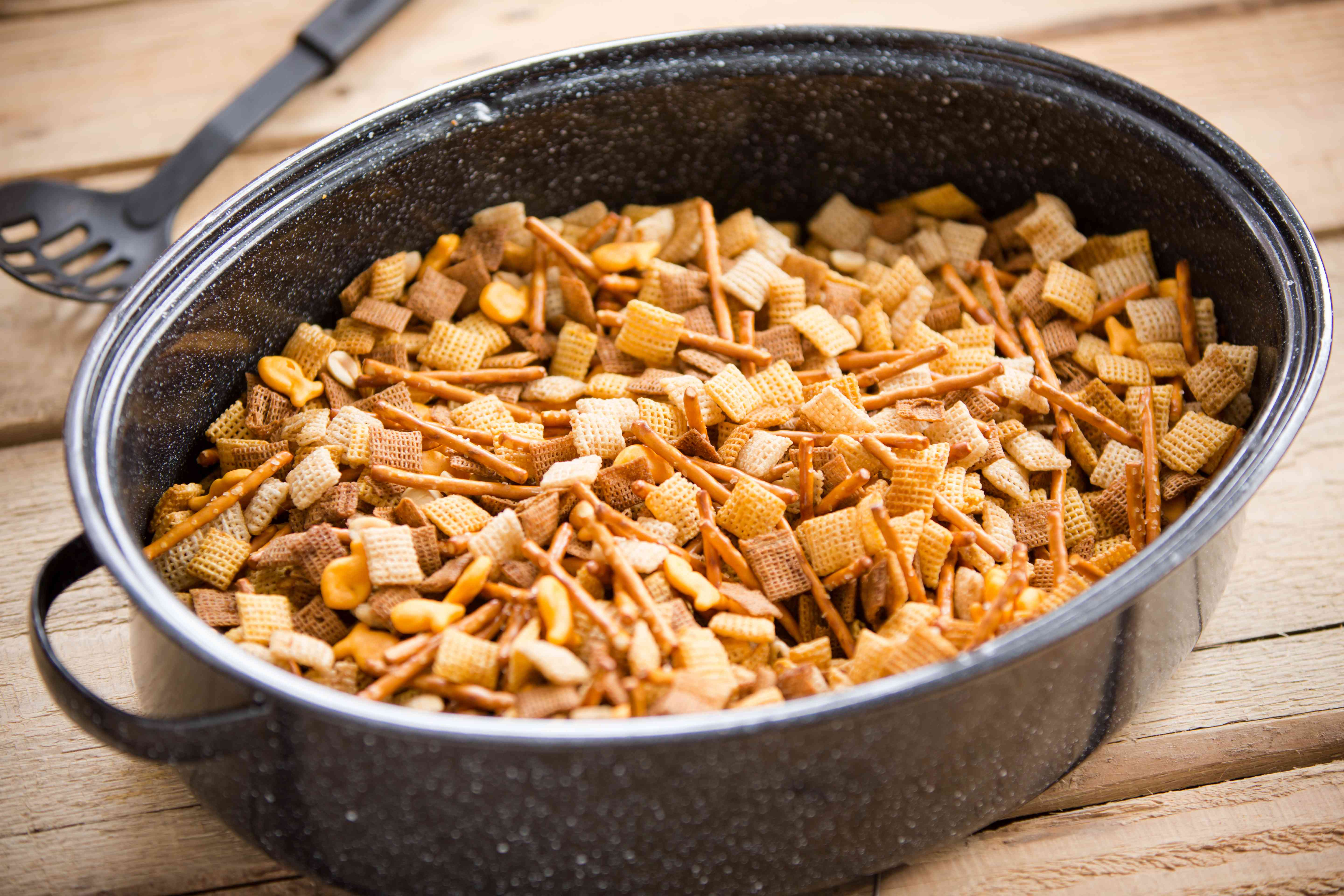 Roaster pan on table full of chex party mix