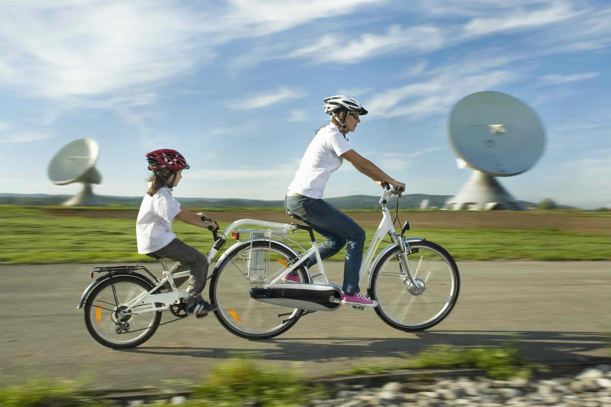 Germany, Bavaria, Raisting, Woman with girl riding electric bicycle near radio station