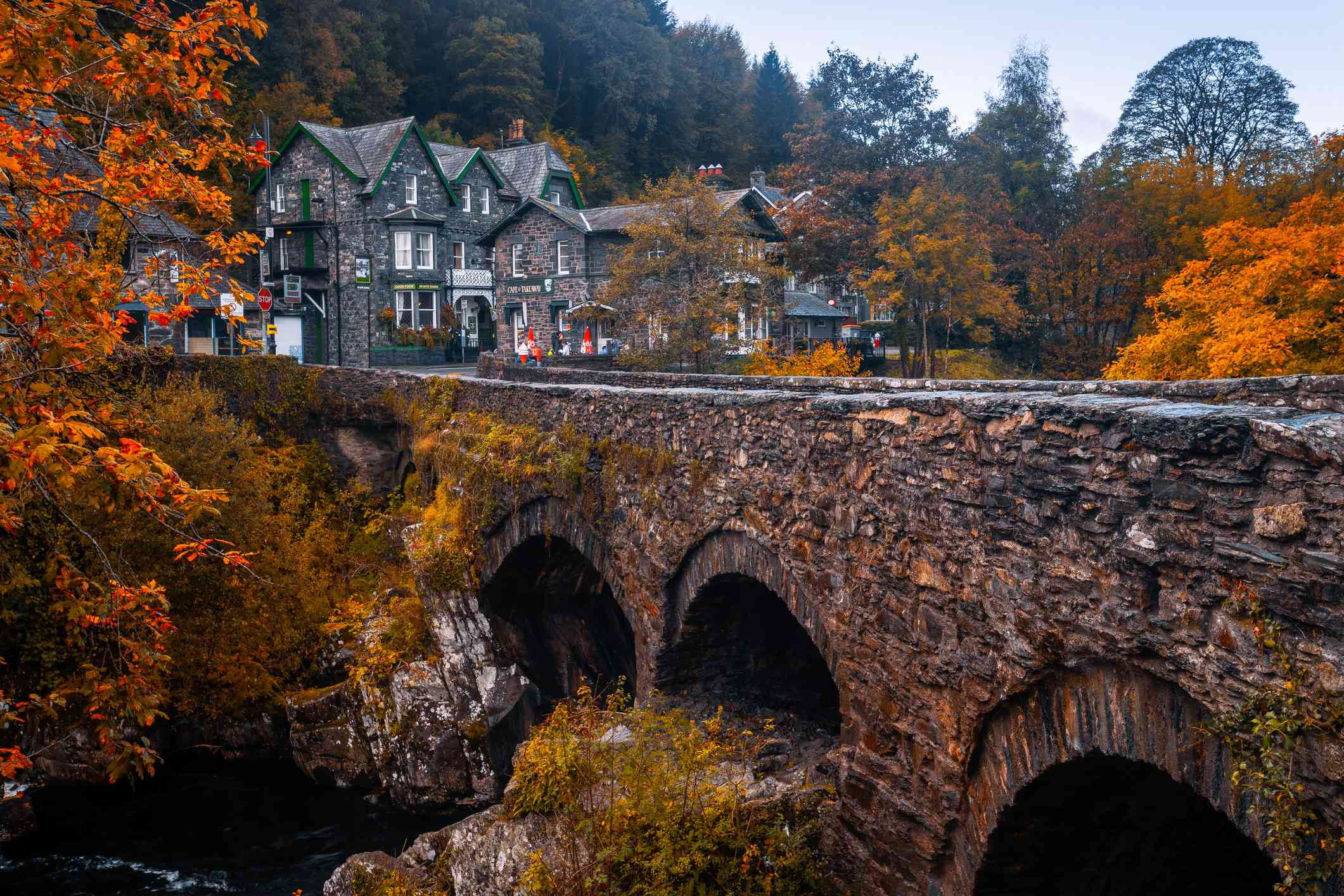 an old stone bridge surrounded by bright orange trees and two cottages with green and gold trees in the background in Snowdonia, Wales