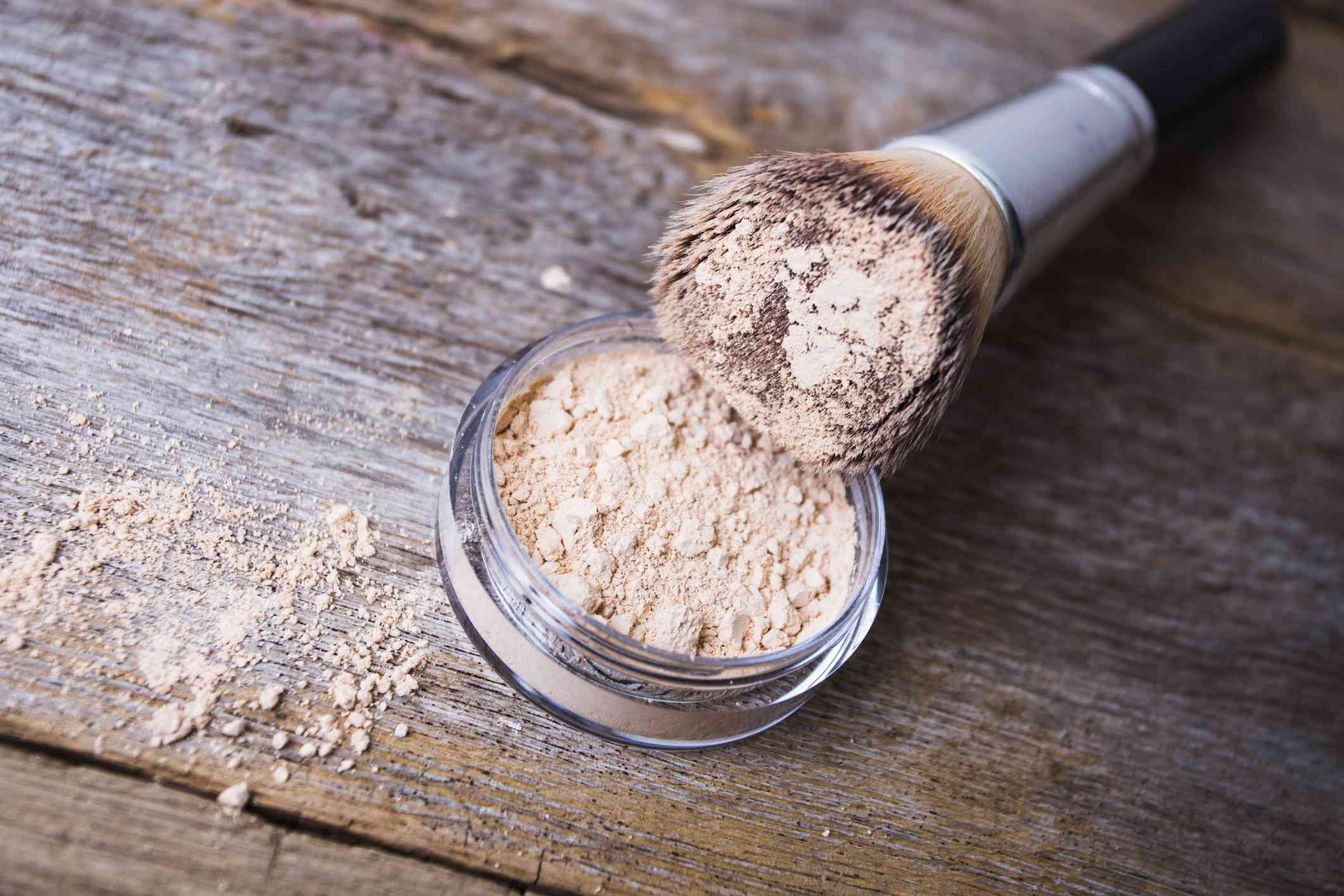 Loose powder on a rustic wood table with brush.