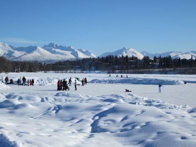 Mounds of snow give way to a frozen lake with dozens of ice skaters on it as snowy mountains loom in the background on a blue-sky afternoon