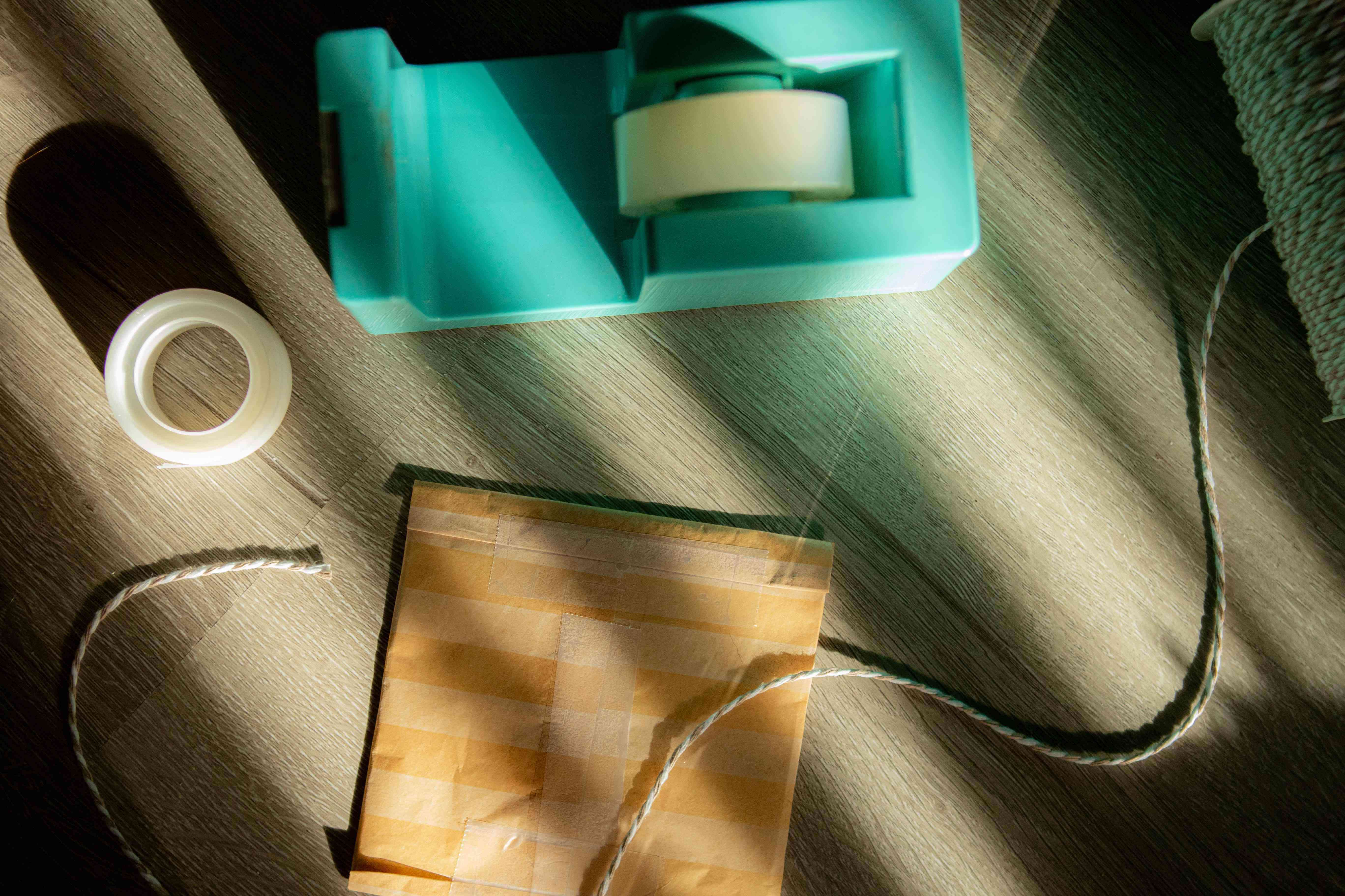teal tape dispenser along with roll of plastic clear tape and flat package