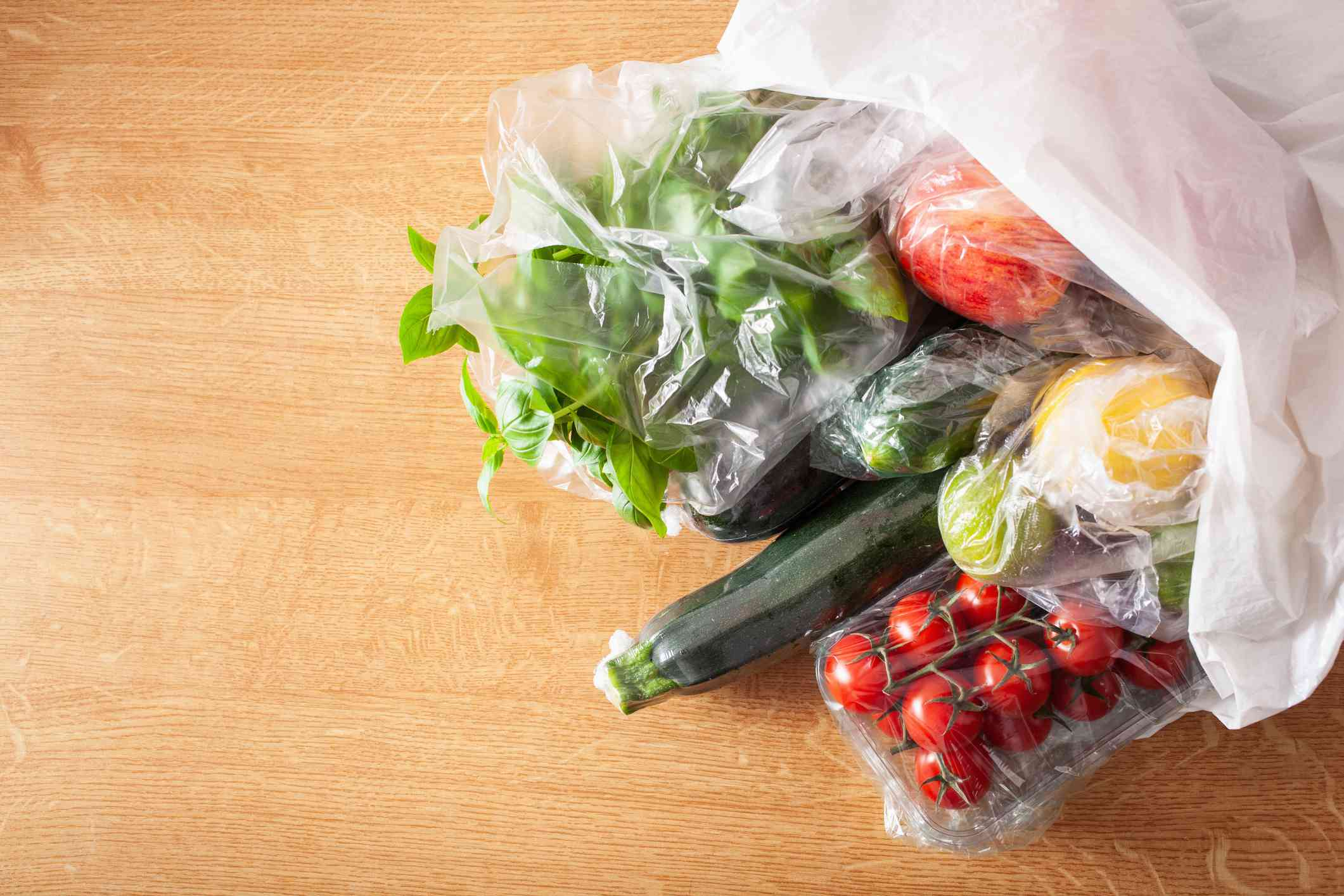 A plastic grocery bag with plastic-covered produce inside.