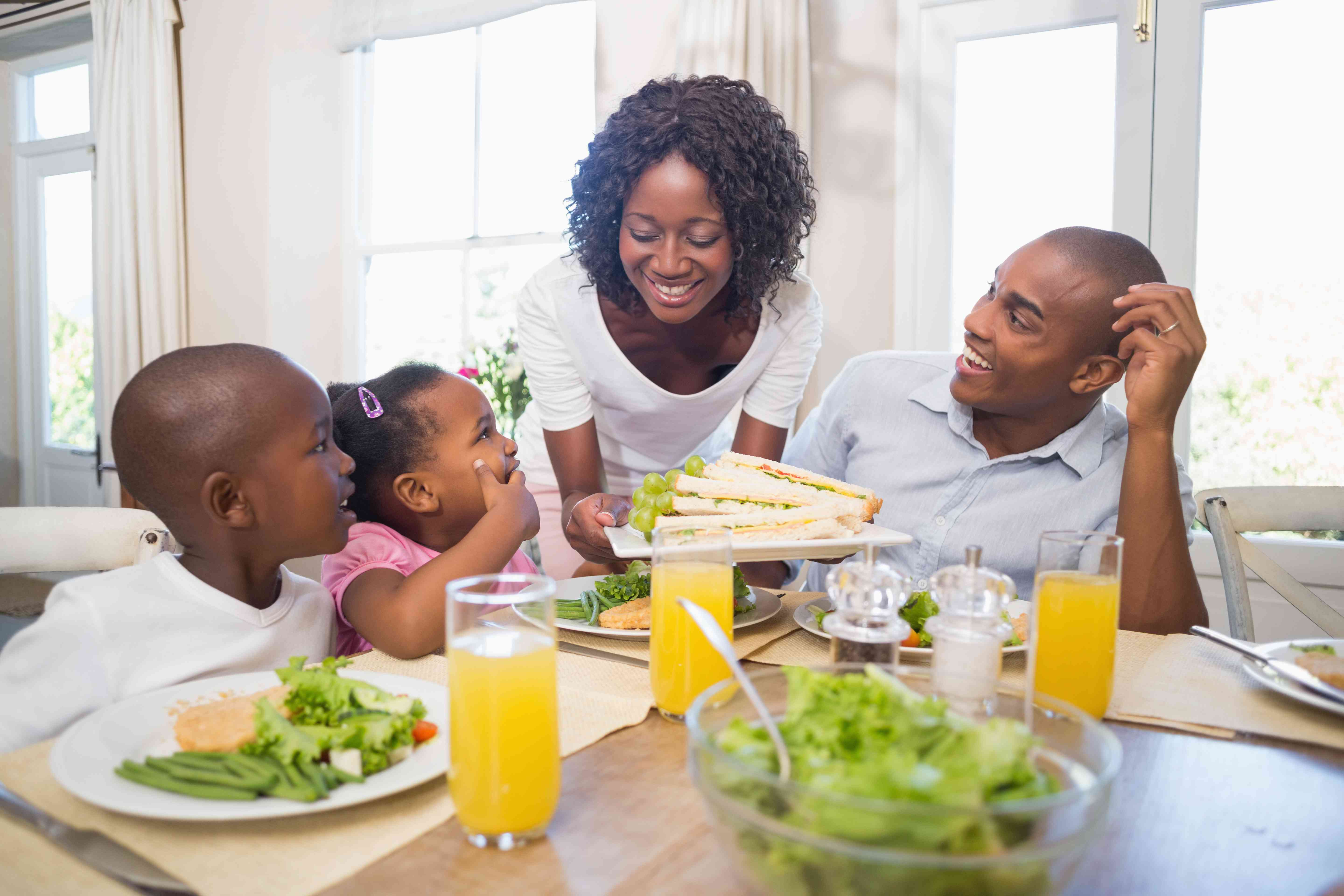 a mom brings food to the dinner table for family