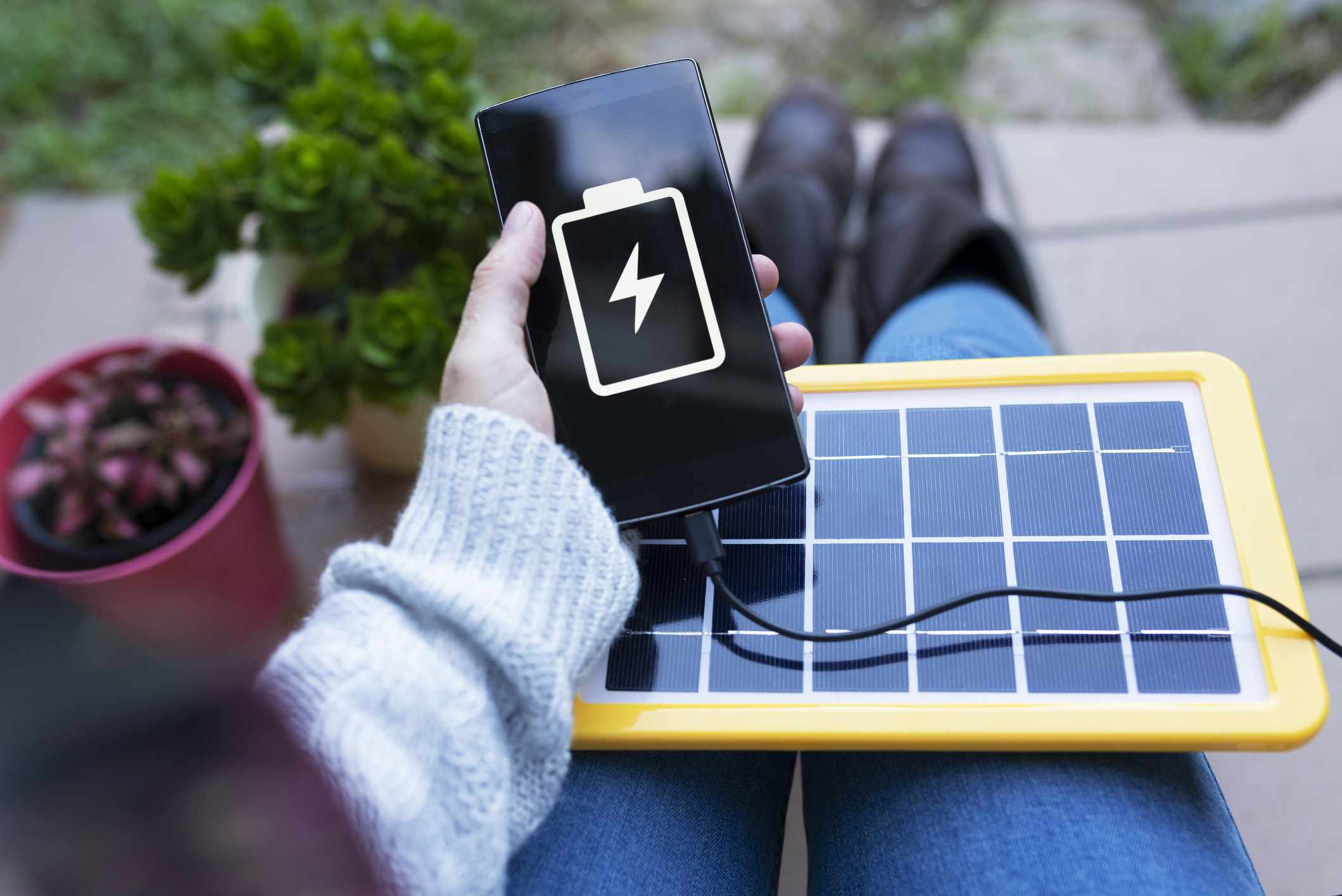 A tablet-sized portable solar device powers a smartphone.
