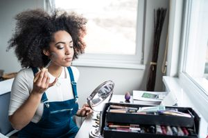 A black woman with afro applies make up in the mirror by window.