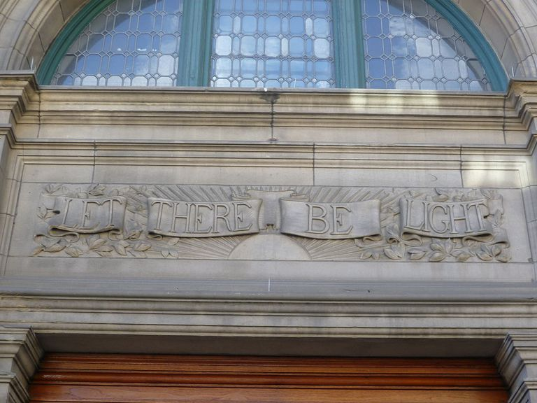 """Building front with """"let there be light"""" in relief against the stone"""
