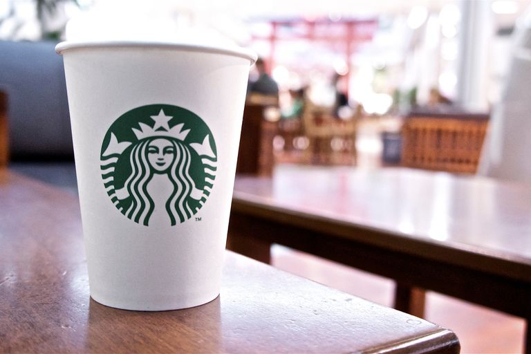Paper Starbucks cup sitting on a table
