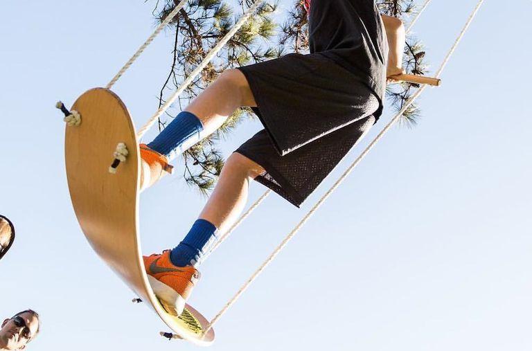 A teenage boy riding a Swurfer outside