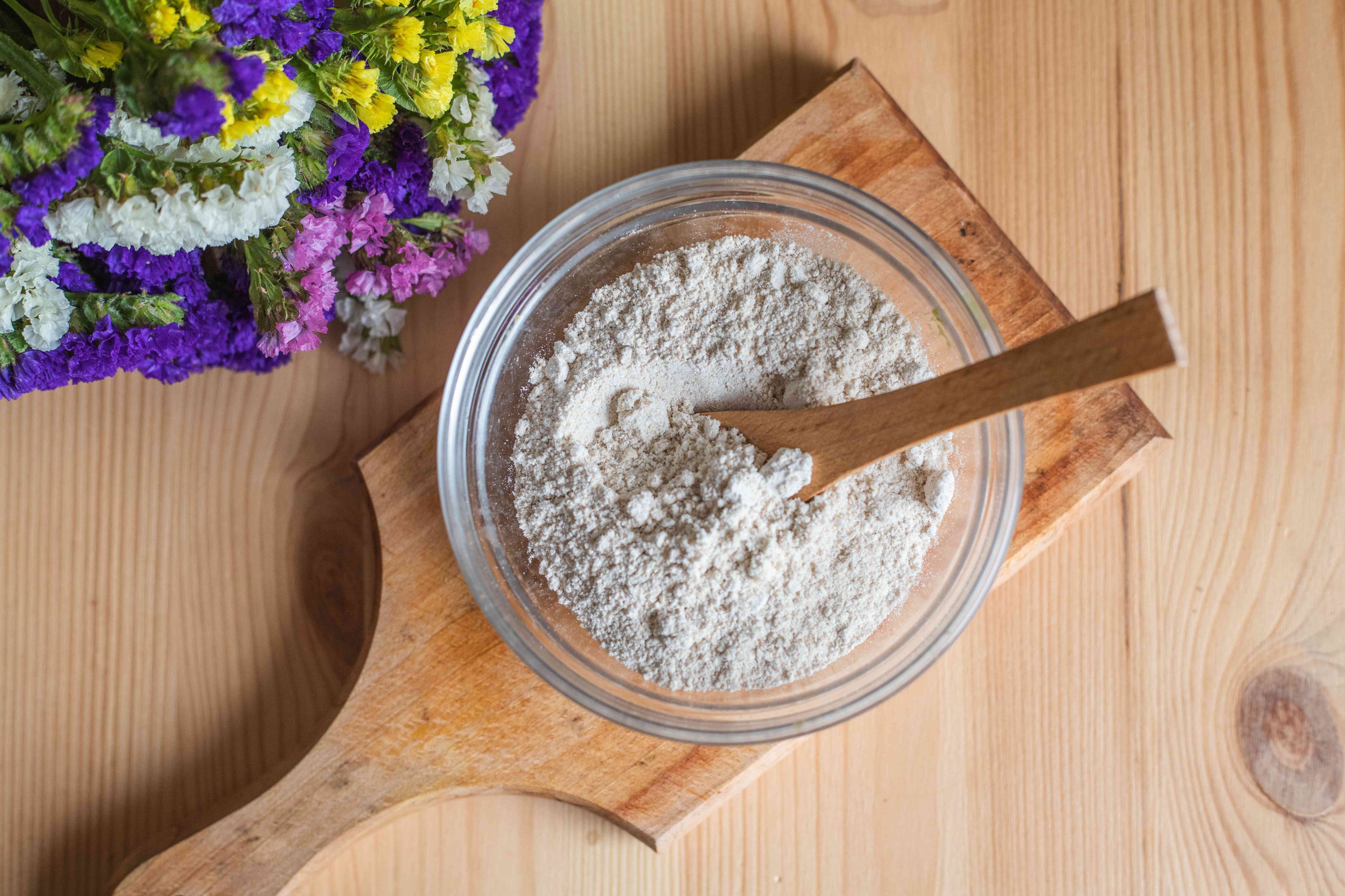 ground rolled oats become colloidal oatmeal in glass bowl with wooden spoon