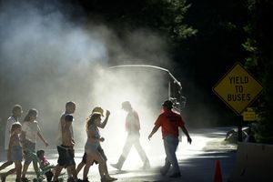 Pedestrians walk through a cloud of dust and diesel exhaust from a transit bus near Yosemite Village, June 16, 2000 in Yosemite National Park, California.