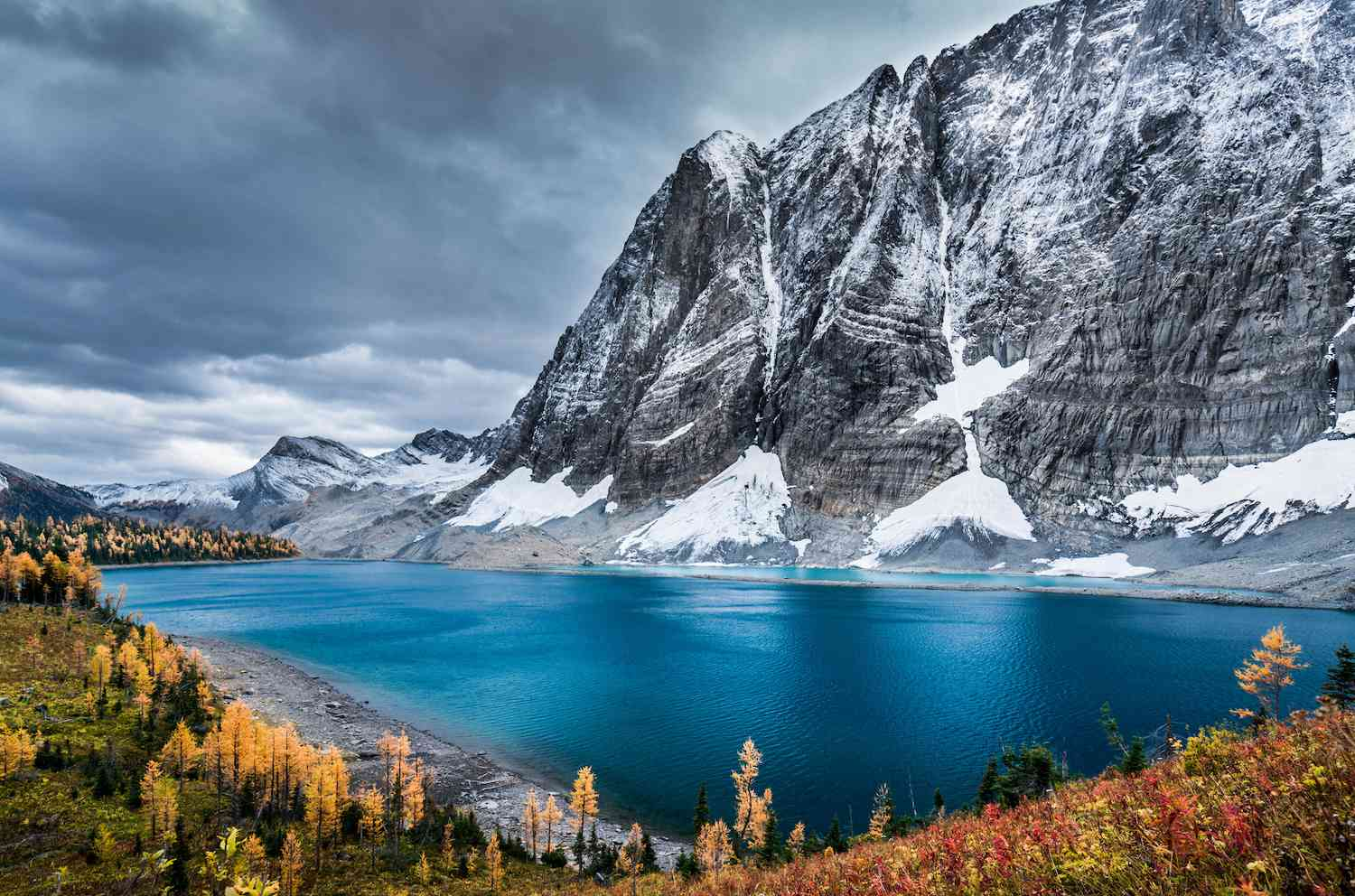 A deep blue lake sits at the base of an icy mountain in Kootenay National Park