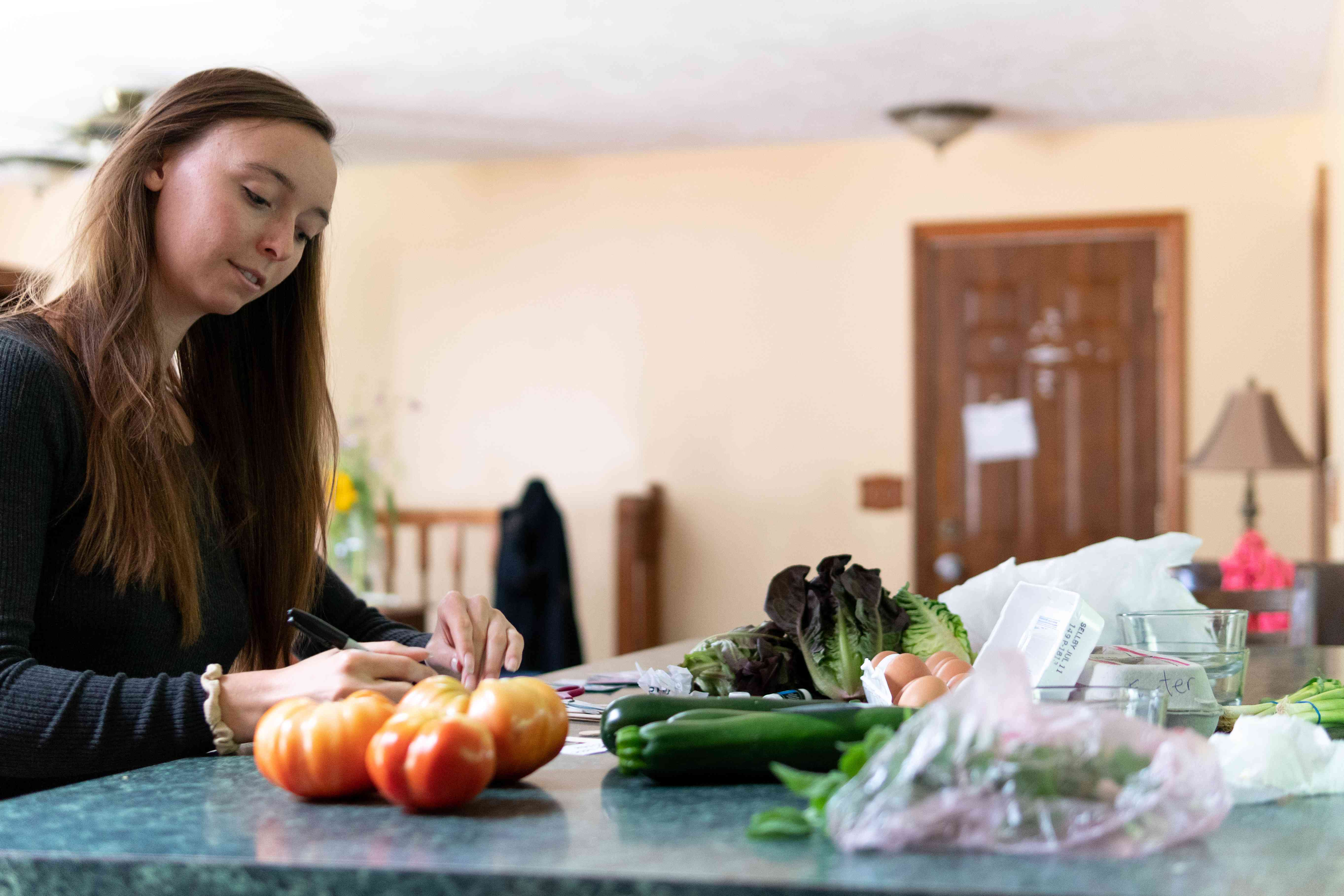 woman writes recipes on counter with veggies