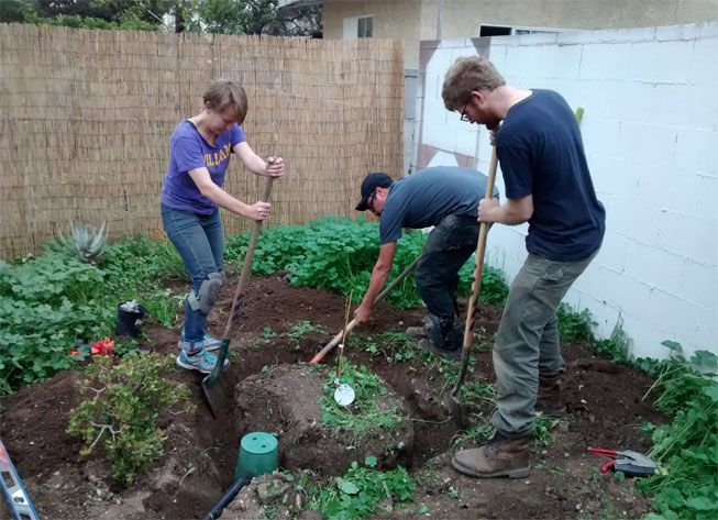 Greywater Action volunteers work to install a grey water irrigation system