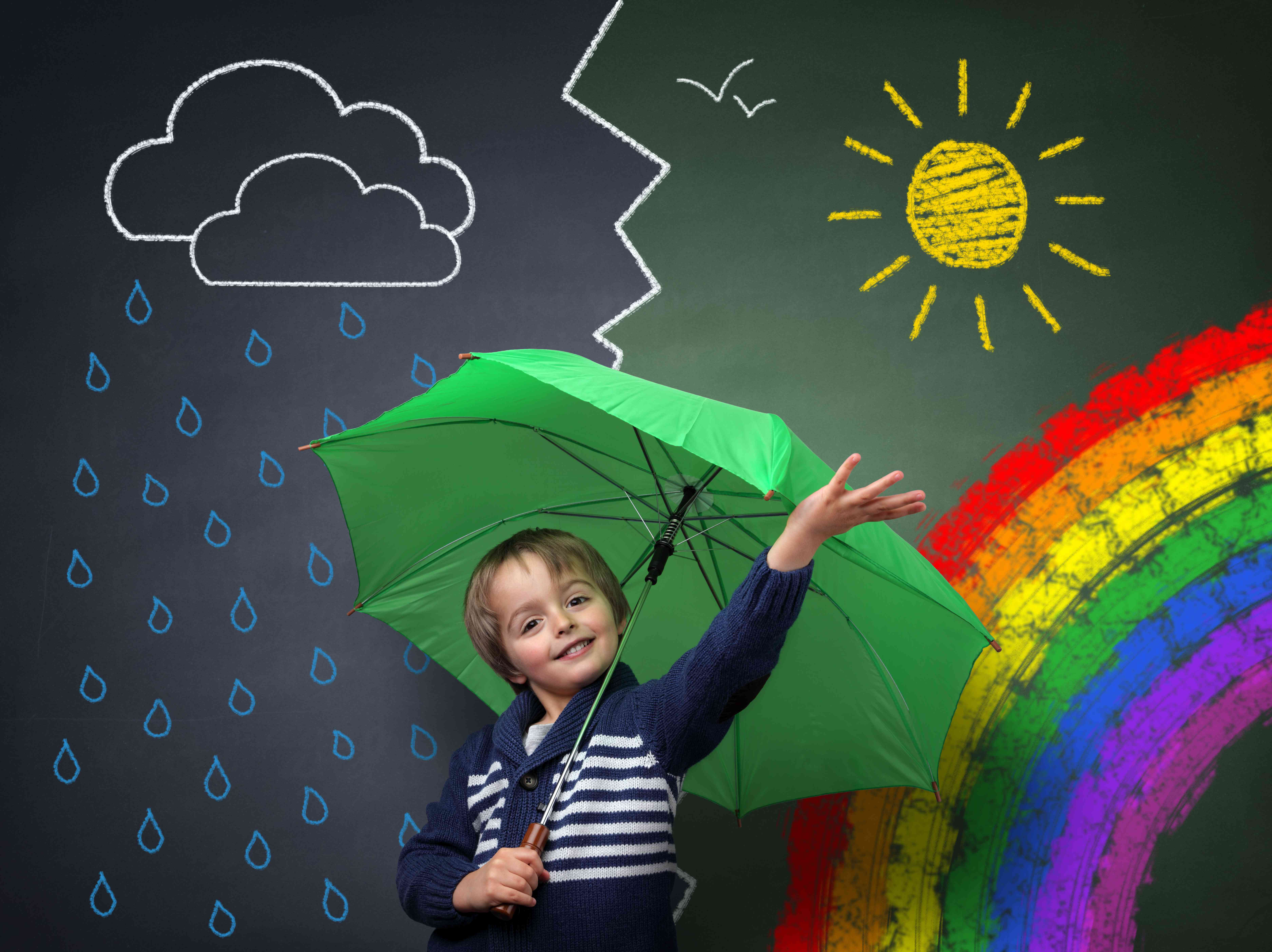 A boy stands under an umbrella in front of a chalkboard