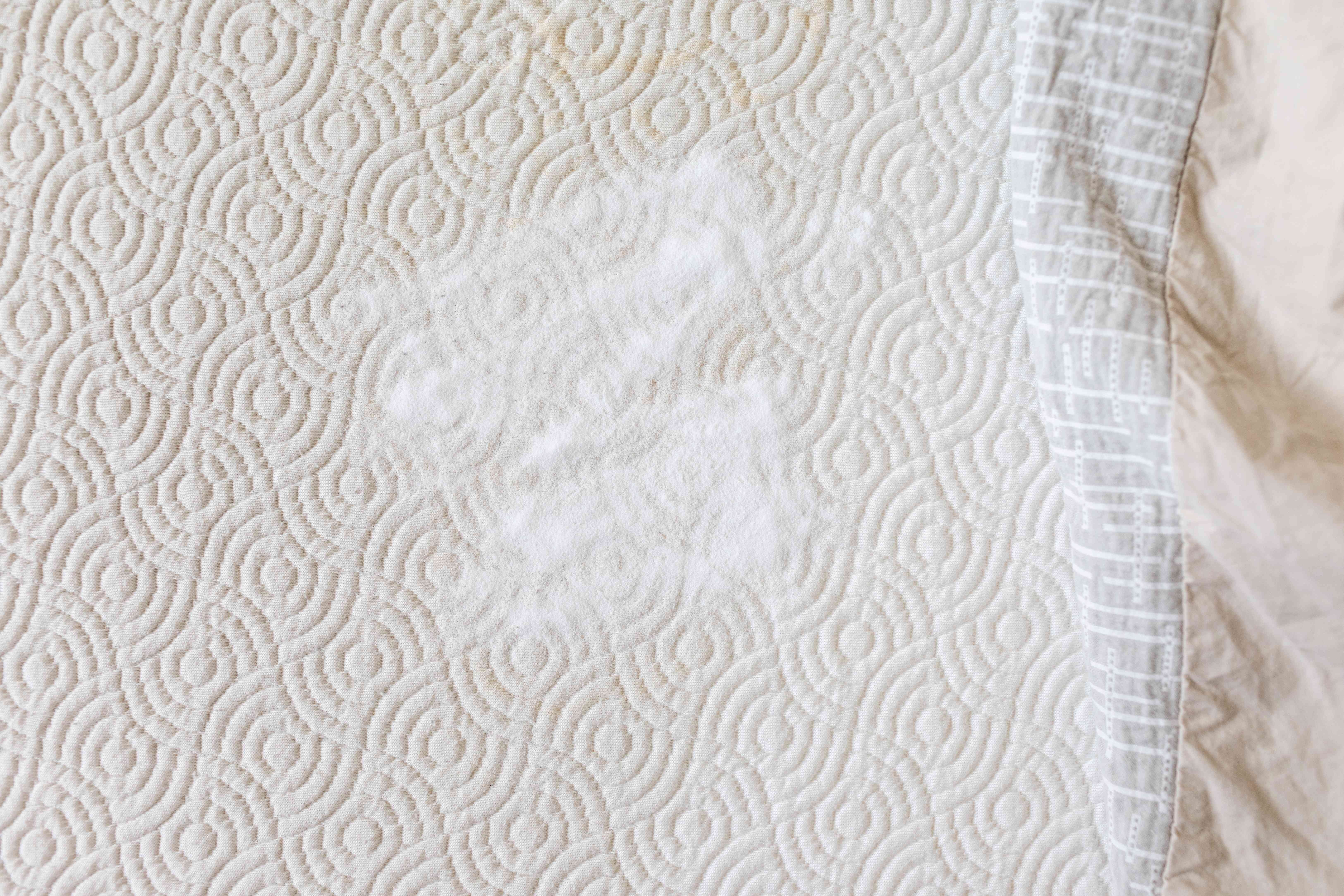 pile of spread-out baking soda on bare mattress with top sheet pulled away
