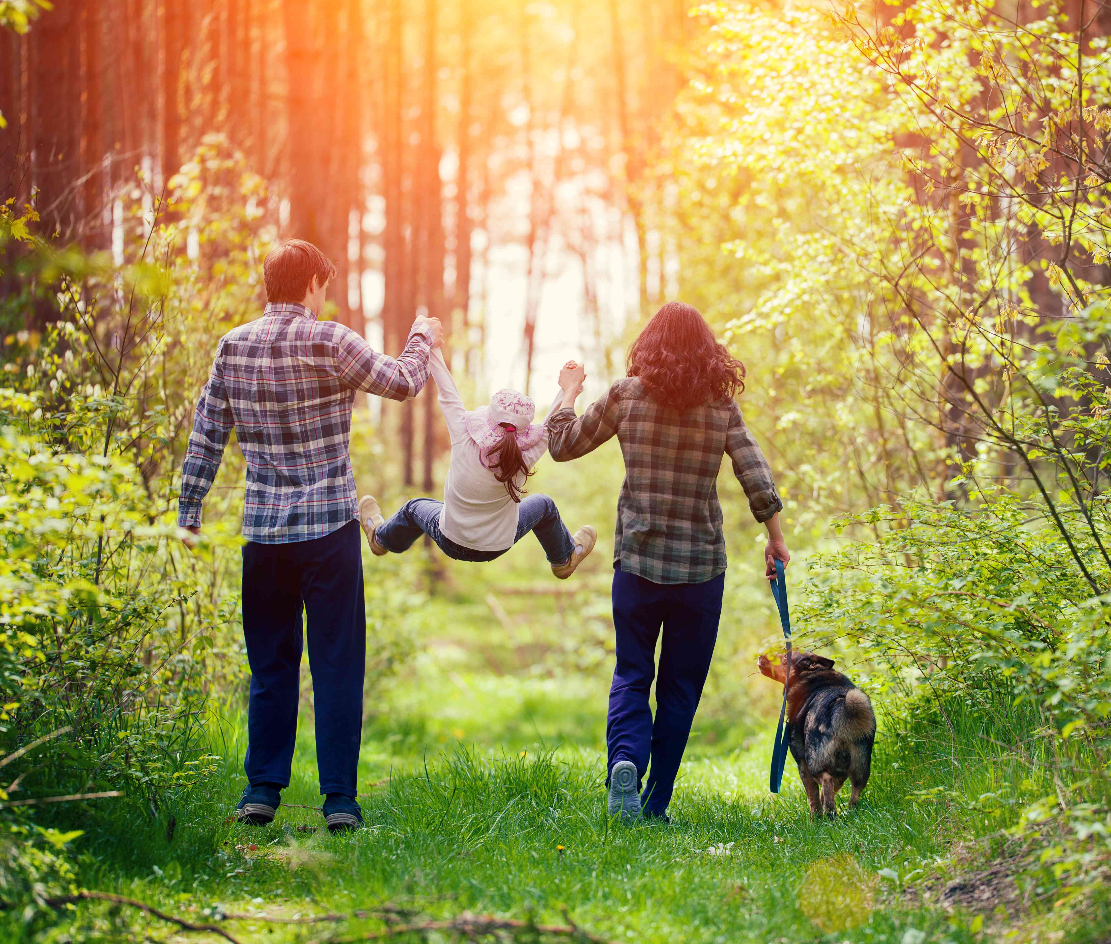 parents and kid and dog in nature
