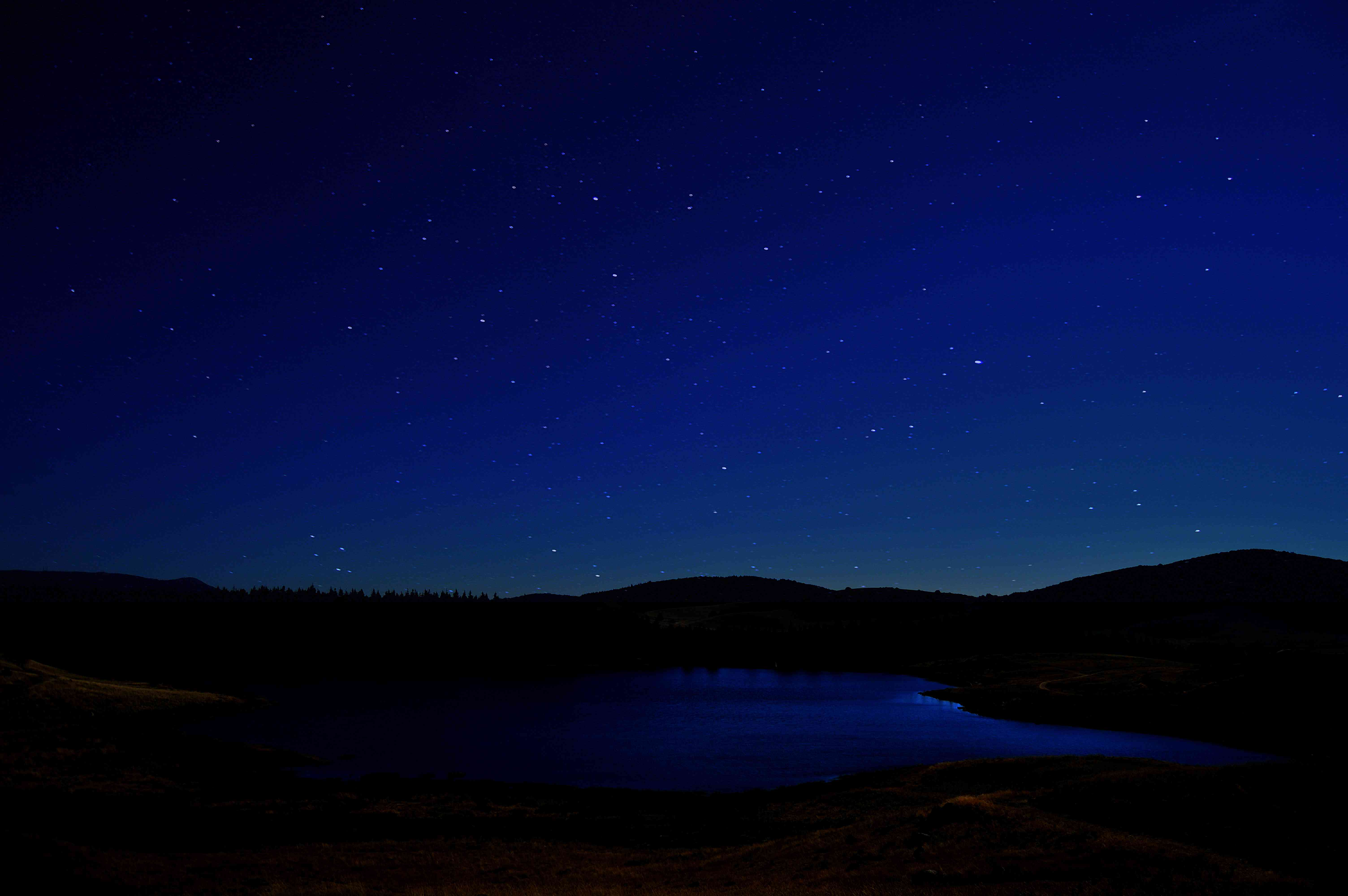 Starry night sky over mountains and lake in Cévennes