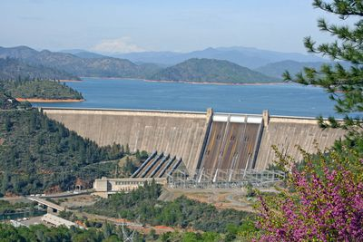 The concrete Shasta Dam surrounded by the bright colors of springtime with Shasta Lake in the background