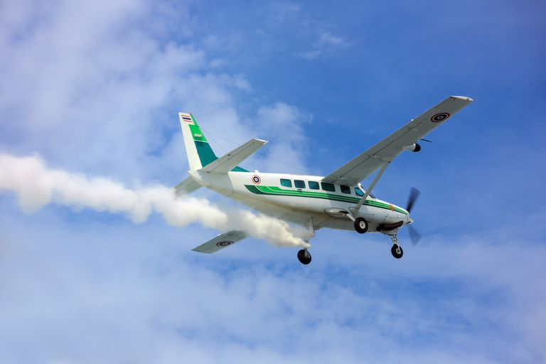 Close-up of a turboprop plane sprinkling chemicals into clouds in a blue sky.