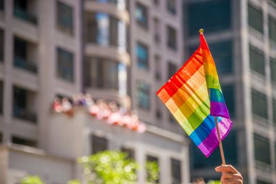 Cropped Hand Holding Rainbow Flag In City