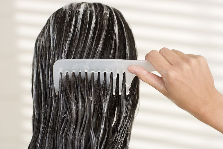 A woman combing conditioner through her dark hair.