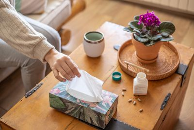 person on couch reaches for kleenex while having allergic reaction to plant