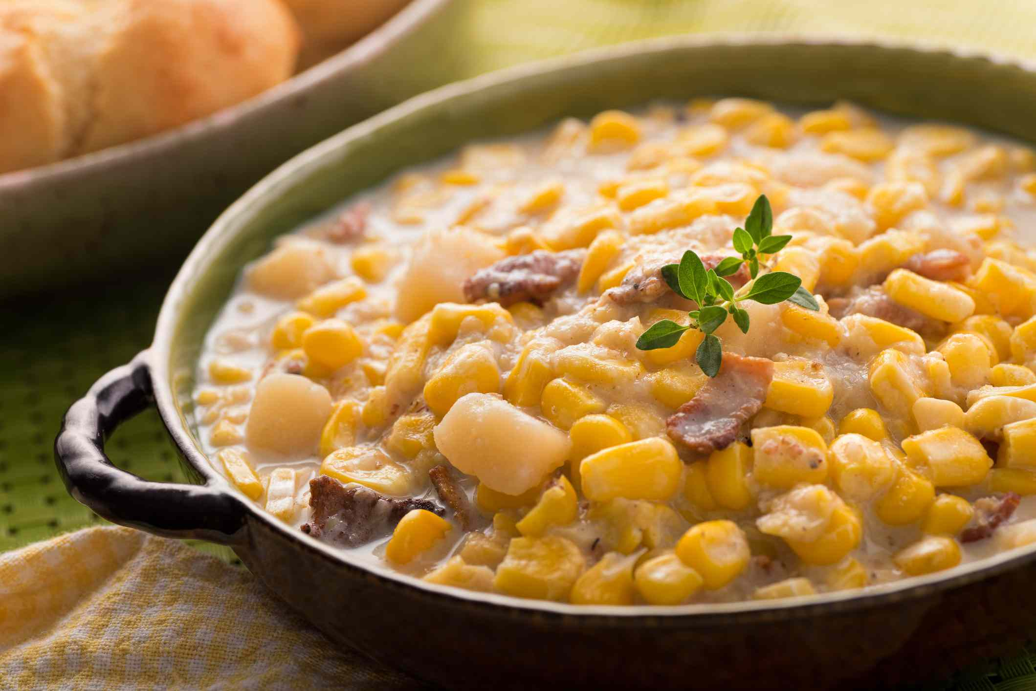 A bowl of homemade corn chowder with bacon, potato, and cheese biscuits