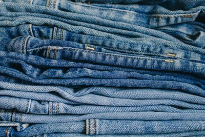 multiple pairs of different denim jeans in different washes stacked on top of each other