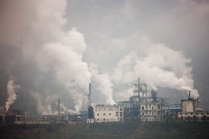 Cement factories with white plumes gas coming out of stacks