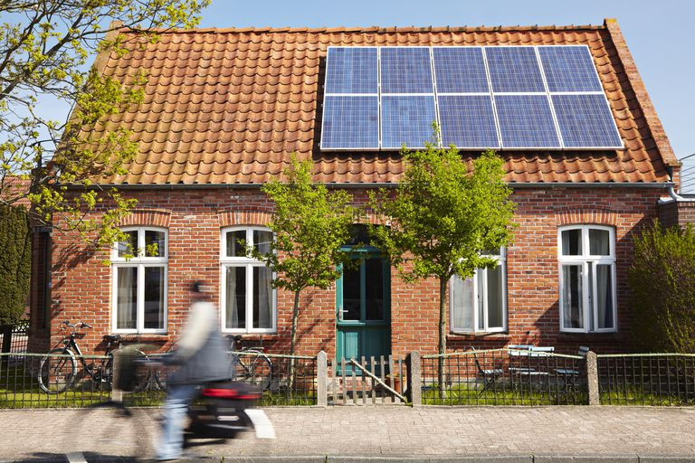 Person riding bike in front of house with solar panels
